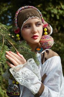 Mädchen in einem handgemachten kleid der ethnischen mode der weinlese, das draußen aufwirft