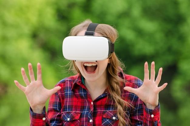 Mädchen in einem helm der virtuellen realität auf der oberfläche der natur. freude