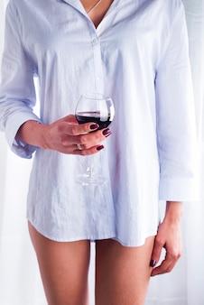 Mädchen in einem hemd mit einem glas rotwein