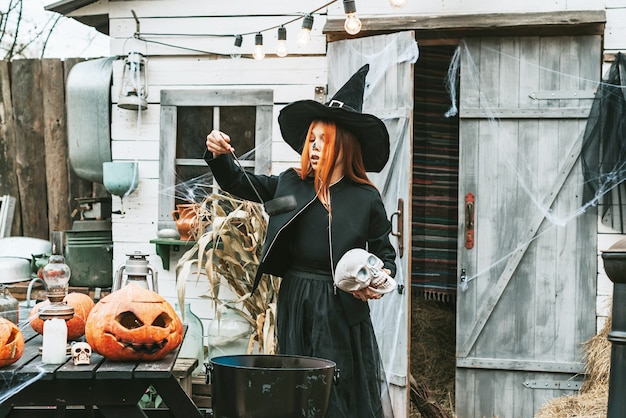 Mädchen in einem hexenkostüm auf einer halloween-party brauen einen trank