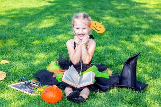 Mädchen in einem hexenkostüm für den halloween-feiertag. plakat mit der aufschrift: halloween. glückliches sitzendes mädchen liest einen zauber aus einem buch und hält einen zauberstab