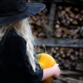 Mädchen in einem hexenkostüm, schwarzem hut, langen weißen haaren, halloween-feiertag