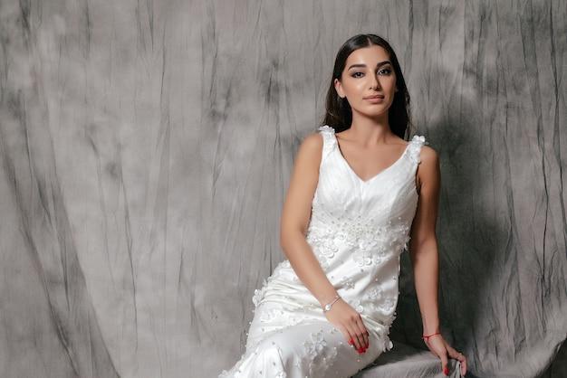 Mädchen in einem hochzeitskleid-studioporträt auf einem grauen hintergrund