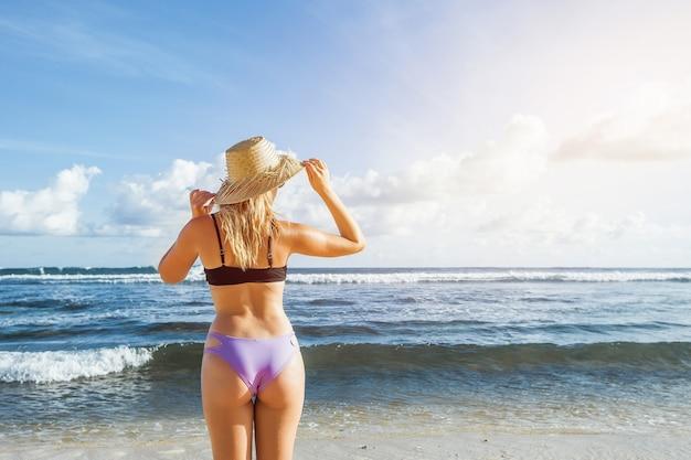 Mädchen in einem hut, der am strand steht und den ozean betrachtet
