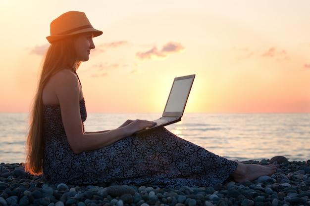 Mädchen in einem hut, der an seinem laptop gegen das meer bei sonnenuntergang sitzt und arbeitet