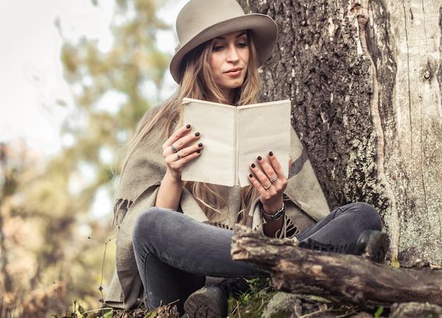 Mädchen in einem hut, der ein buch im herbstwald liest