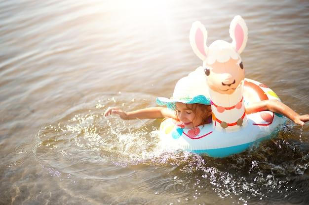 Mädchen in einem hut, der im fluss mit aufblasbarem kreis in form eines lamas schwimmt. aufblasbares alpaka für ein kind. meer mit sandigem grund. strandurlaub, schwimmen, bräunen, sonnencreme.