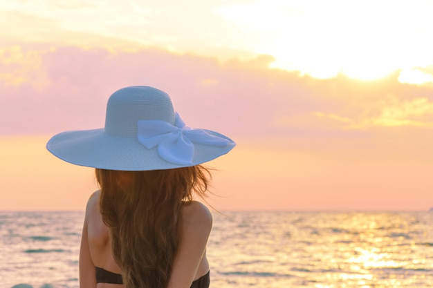 Mädchen in einem hut, hintere ansicht. sonnenaufgang am meer. das konzept der harmonie, ruhe, schönheit, weicht den fokus