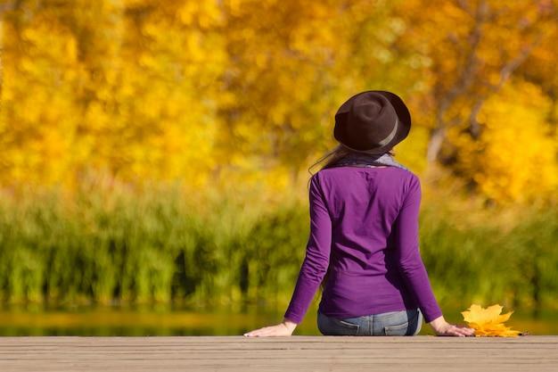 Mädchen in einem hut sitzt auf dem dock und bewundert die farben des herbstes.