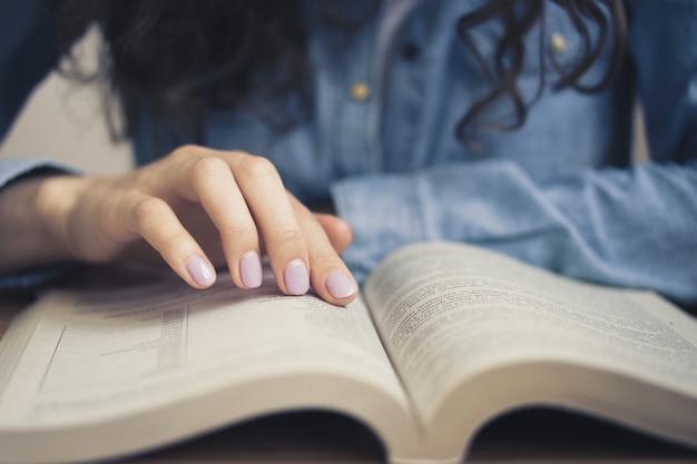 Mädchen in einem jeanshemd liest ein buch