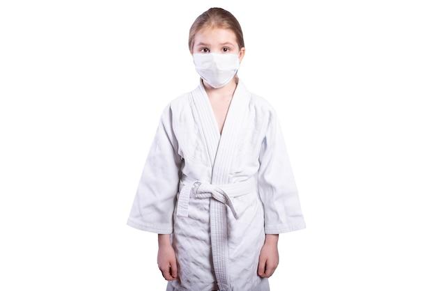 Mädchen in einem kimono-judo. in einer maske ausgebildet. isoliert auf weißem hintergrund. foto in hoher qualität