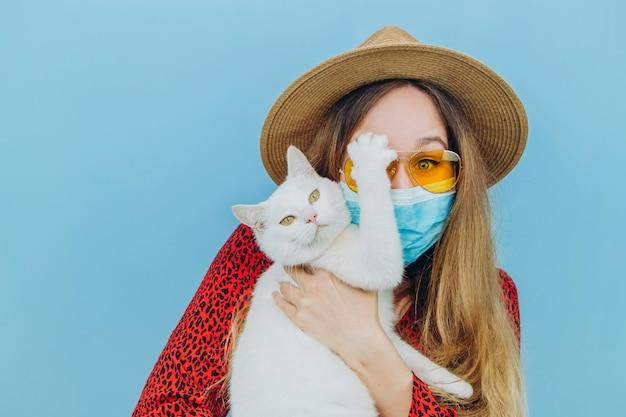 Mädchen in einem kleid, hut und sonnenbrille mit einer medizinischen maske auf ihrem gesicht. urlaub in der epidemie des coronavirus. selbstisolation mit haustieren. das mädchen hält eine weiße katze in den armen. covid 19