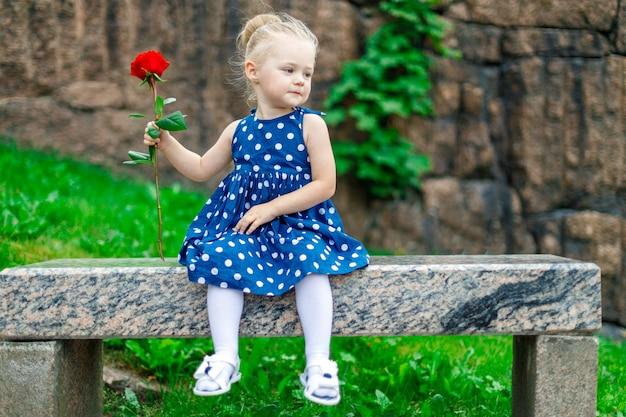 Mädchen in einem kleid mit einer rose in ihren händen
