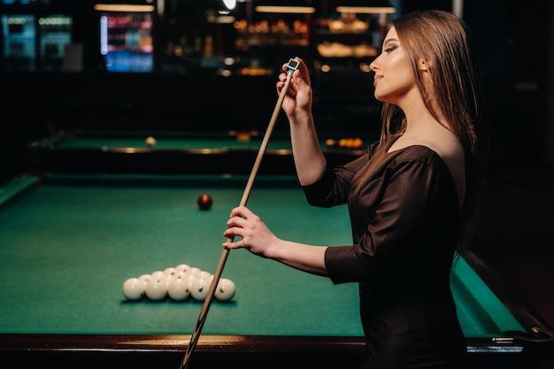 Mädchen in einem kleid steht mit einem queue in den händen und reinigt es mit kreide in einem billardclub