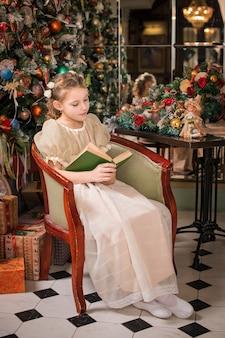 Mädchen in einem kühlen kleid sitzt in einem sessel nahe dem weihnachtsbaum und liest ein buch