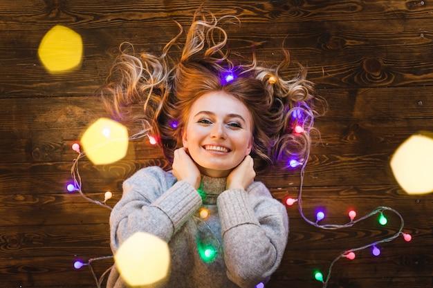 Mädchen in einem langen hellen pullover, einer jacke und einer girlande mit weihnachtslichtern