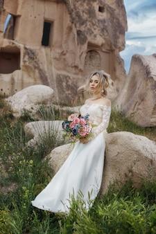 Mädchen in einem langen hochzeitskleid mit einem blumenstrauß in den händen sitzt in den bergen in der natur. hochzeit in natur, beziehungen und liebe. berge von kappadokien in der türkei