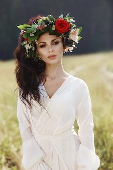 Mädchen in einem langen kleid steht in einem feld mit kranz auf dem kopf und blumenstrauß in den händen, schöne frau in den strahlen der abendsonne im herbst im dorf