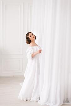 Mädchen in einem langen weißen kleid in einem hellen raum