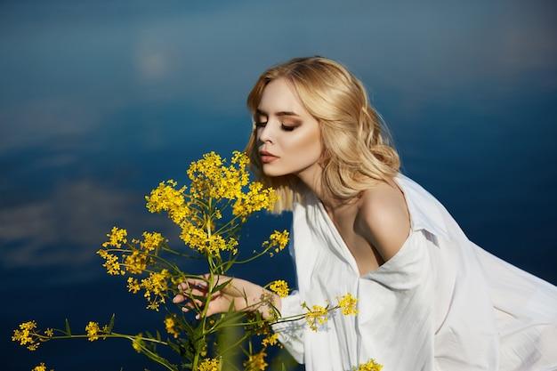 Mädchen in einem langen weißen kleid mit einer blume in ihrer hand steht nahe dem see. blonde frau in der sonne in einem hellen kleid. stillstehendes und träumendes mädchen, perfektes sommermake-up auf ihrem gesicht