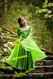 Mädchen in einem märchenhaften elfenkleid geht barfuß durch den wald und geht die runen einer alten treppe hinunter