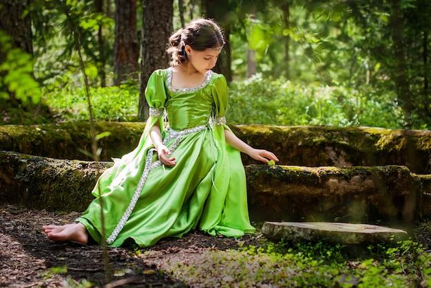 Mädchen in einem märchenhaften elfenkleid sitzt barfuß auf den alten ruinen im wald und spielt mit einem schmetterling