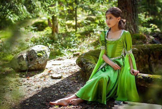 Mädchen in einem märchenhaften elfenkleid sitzt barfuß auf den runen einer alten treppe