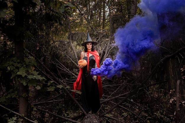 Mädchen in einem magischen wald mit farbigem rauch.