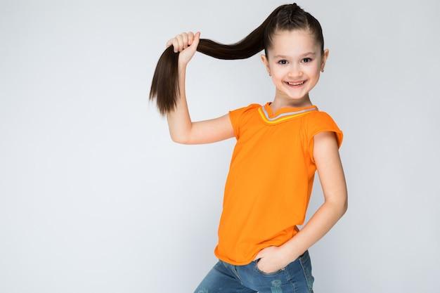 Mädchen in einem orangefarbenen t-shirt und blue jeans
