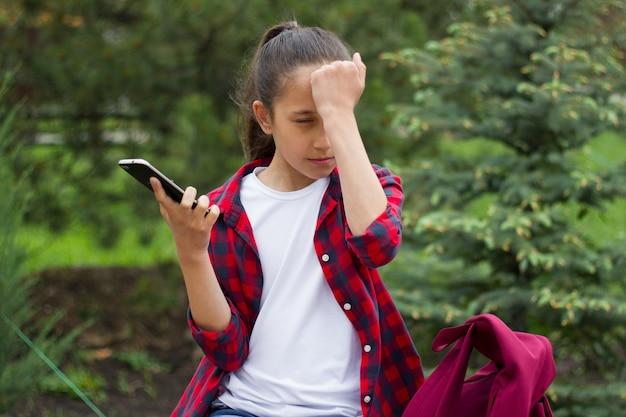 Mädchen in einem park hält ein telefon in der hand benutzt es, um sich selbst schläge auf die stirn zu kommunizieren