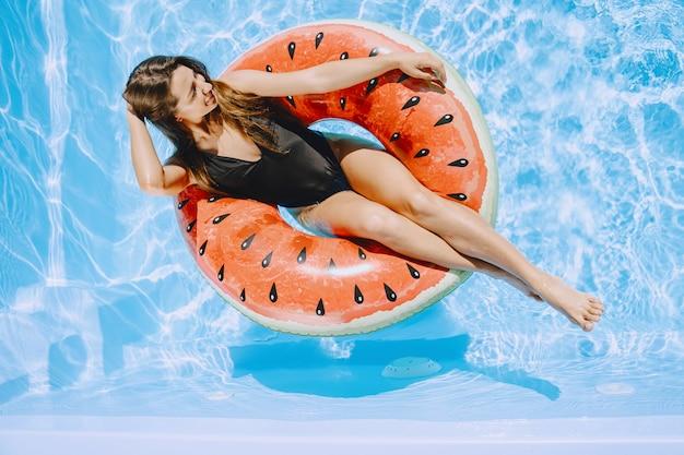 Mädchen in einem pool. frau in einem stilvollen badeanzug. dame in den sommerferien