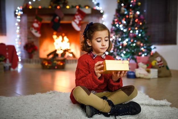 Mädchen in einem raum für weihnachten dekoriert mit goldenen geschenkkarton