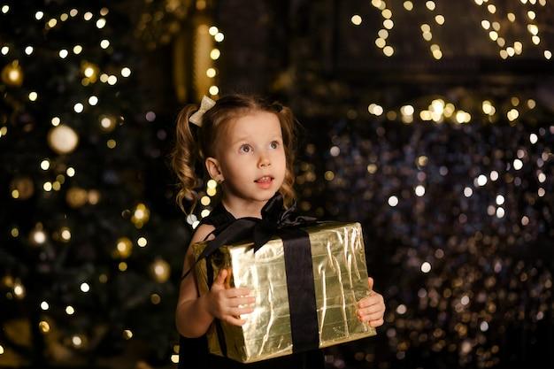 Mädchen in einem raum mit funkelnder golddekoration, die ein weihnachtsgeschenk hält