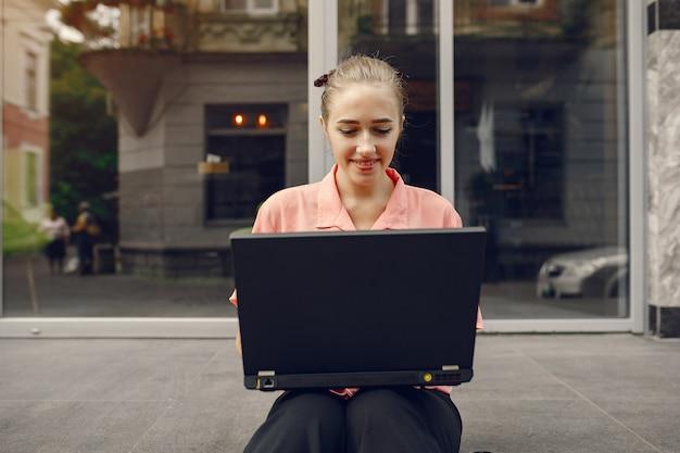 Mädchen in einem rosa hemd, das nahe haus sitzt und den laptop benutzt