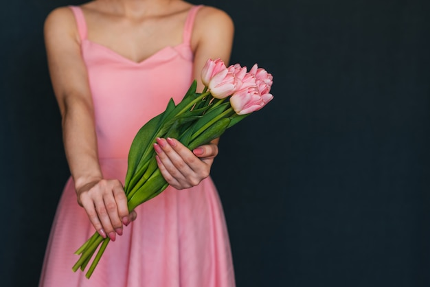 Mädchen in einem rosa kleid, das einen blumenstrauß von tulpen hält