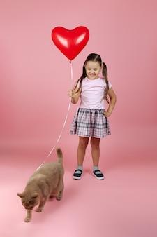 Mädchen in einem rosa kleid mit einem roten ballon in form eines herzens spielt mit einer roten britischen katze