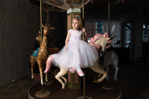Mädchen in einem rosa kleid und einer krone auf einem karussell mit einem weißen pony