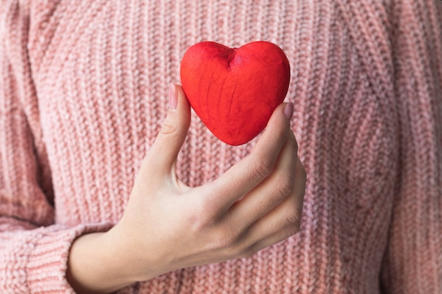 Mädchen in einem rosa pullover hält ein rotes herz in der hand, das konzept einer liebeserklärung.