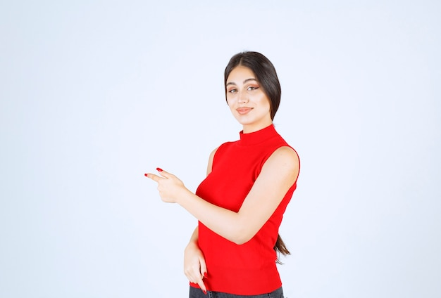 Mädchen in einem roten hemd, das auf die linke seite zeigt.