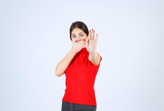 Mädchen in einem roten hemd, das etwas mit den händen stoppt