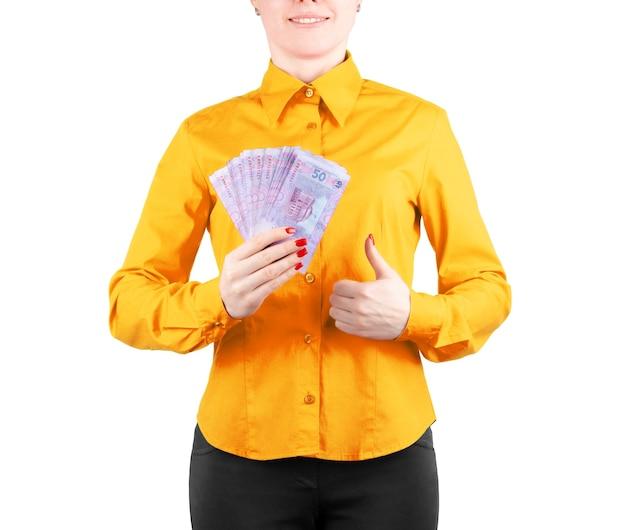 Mädchen in einem roten hemd hält geld in den händen auf weißem hintergrund
