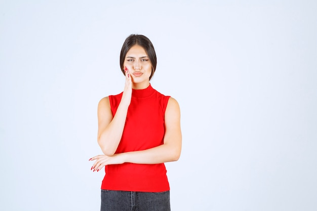 Mädchen in einem roten hemd sieht verängstigt und verängstigt aus.