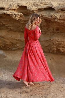 Mädchen in einem roten kleid bei den felsen