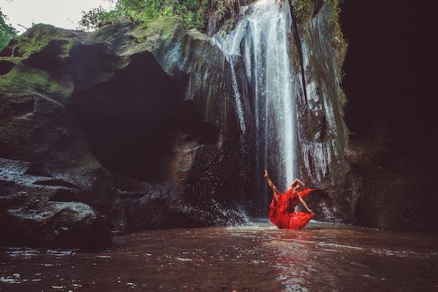 Mädchen in einem roten kleid, das in einem wasserfall tanzt.