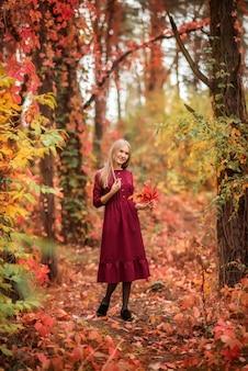 Mädchen in einem roten kleid im herbstwald. ein wunderschöner märchenwald. ein blumenstrauß in deinen händen