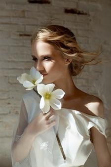 Mädchen in einem schicken langen kleid, das auf dem boden sitzt. weißes hochzeitskleid
