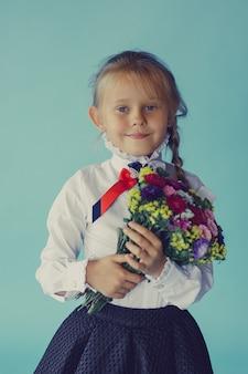 Mädchen in einem schulrock und einer bluse, die mit blumenstrauß aufwerfen. zurück zur schule