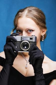 Mädchen in einem schwarzen abendkleid und langen handschuhen hält eine film-langstreckenkamera in den händen