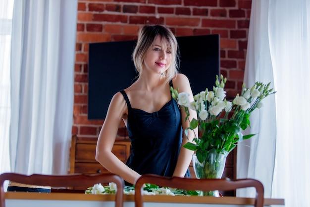 Mädchen in einem schwarzen kleid hält weiße rosen, bevor sie in eine vase setzen