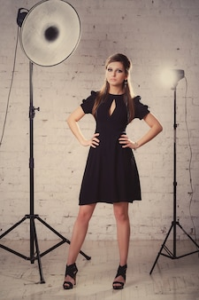 Mädchen in einem schwarzen kleid steht im studio auf dem weißen backsteinmauerhintergrund